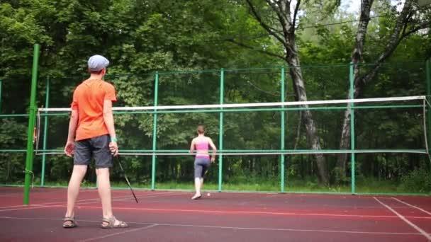 Chlapce hrát badminton v venkovní sportoviště s matkou
