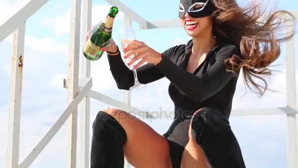 Katze im schwarzen Kostüm lacht und gießt Wein aufs Dach
