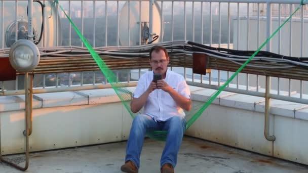 Muž sedící v houpací síti na střeše a fotografování na svém telefonu na narozeninovou oslavu