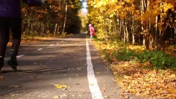 Ženy na kolečkových bruslích s javorový list v rukou na trať v lese