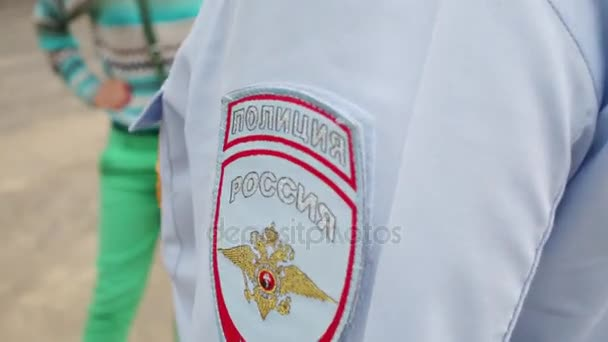 Shoulder of policemen with stripe and badge on chest. Text: Russian Interior Ministry, police