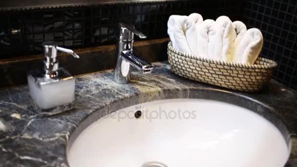 Detail umyvadla s chrome kohoutek a krásné zrcadlo