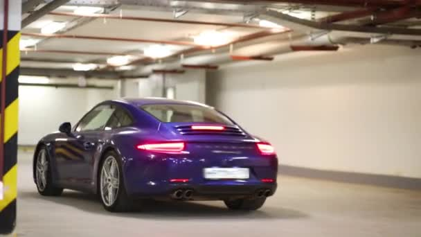 Blue sports car with burning rear lights in underground parking