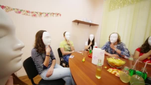 Ten young people hide faces by masks and sit at table