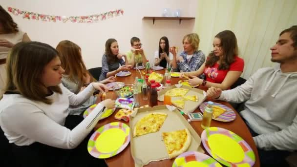 Eleven teenagers sit at table and eat pizza during birthday