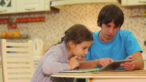 Uomo e ragazza sedersi a un tavolo e guarda nel tablet