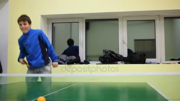 Šťastný chlapec dospívající hraje stolní tenis na zeleném stole