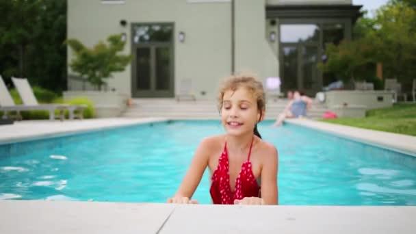 Šťastná dívka v červených plavkách spočívá ve venkovním bazénu nedaleko domu