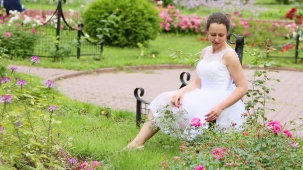 Žena v bílých šatech dotýká květina záhonu růží na trávě v parku.