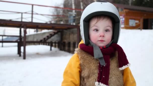 Cute little girl in helmet stands outdoor at winter day