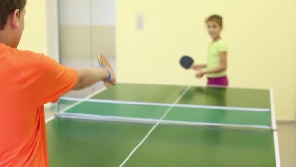 Chlapec a dívka hraje ping pong ve světlé místnosti, se zaměřují na chlapce