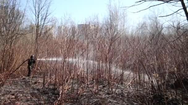 Hasič v uniformě drží hadici a uhasit lesní požár
