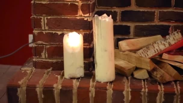 White candles, firewood and lamp near brick fireplace