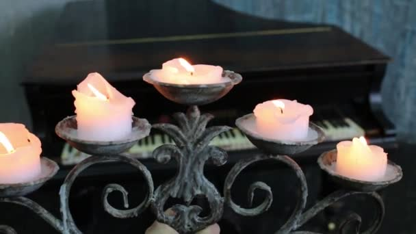 Candles on old wrought-iron candlestick in hand and grand piano