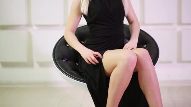 Close up of legs of woman in black dress sitting on chair