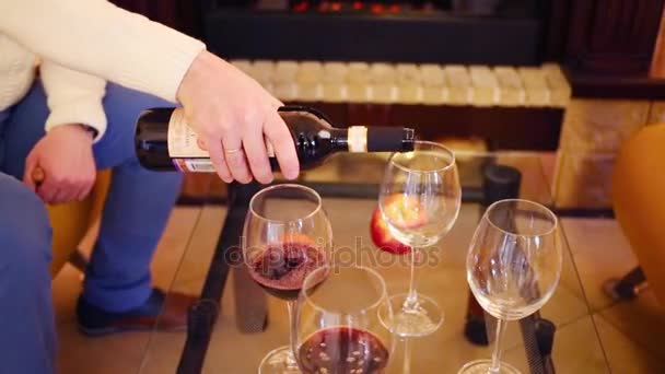 Mužské ruky nalévá červené víno ve čtyřech brýle na skleněný stůl