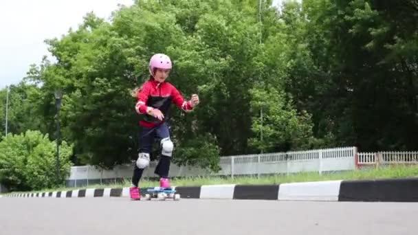 das Mädchen auf einem Skateboard auf dem Gelände neben einem Park an einem Sommertag