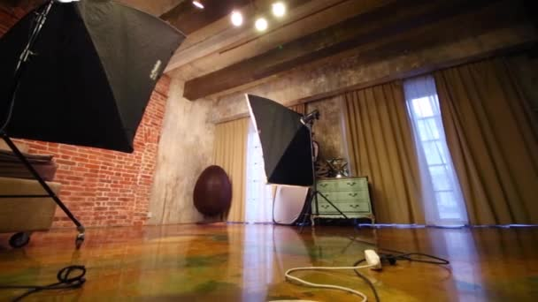 Empty studio with bed, stylish armchair and equipment for shooting