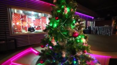 Christmas tree with illuminations and interior of restaurant and with red sofas