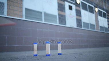 Both poles flying past figures of spaced vertical sticks on pavement in gorodki game.