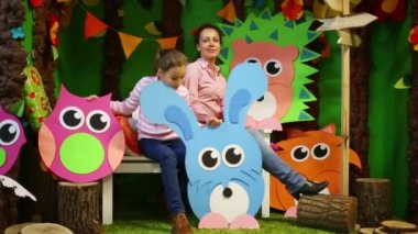 Mother and girl sit among big cardboard animals and trees