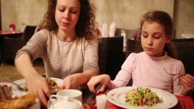Curly woman with her daughter sit in cafe and eat salad
