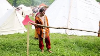 MOSCOW - JUNE, 6, 2015: Two men in robes of ancient people make fence on historical festival in Kolomenskoye. Kolomenskoye is state art and historical, architectural and landscape museum-reserve.