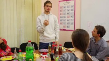Five teenagers sit at table, eat and play pantomime game at birthday, boy depicts object. The text on wall: English alphabet