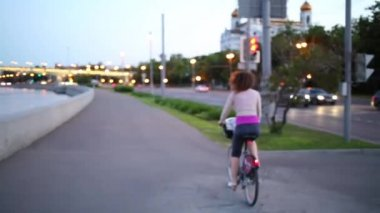 Woman riding bicycle along seafront to bridge next to Cathedral of Christ Savior.