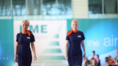 MOSCOW, RUSSIA - JULY 9, 2015: Two girls in uniform Nordavia airlines at the fashion show DME Runway in airport Domodedovo