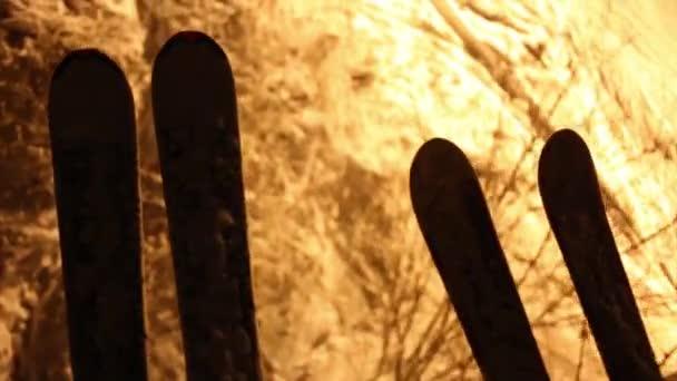 Zwei Paar Ski bewegt sich über Bäume und Schnee auf Seilbahn in der Nacht