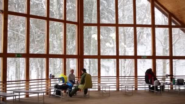 Nelze rozpoznat lidé sedí poblíž velké okno v hale v zimě. Text na zdi: exit