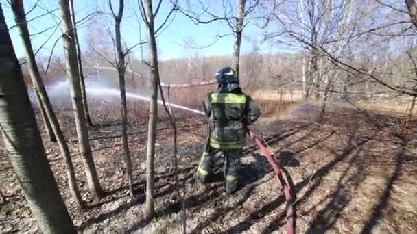 Hasič v ohnivzdorné uniformě uhasit lesní požáry. Text na zadní: hasiči, Ruské ministerstvo Emergency