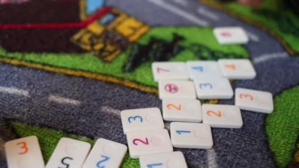 Fiú játszik a padlón - eltolódások számok chipek a padlón, látható csak kézzel