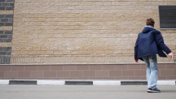 Zadní chlapce v džínách školení hrát tenis zdi venkovní