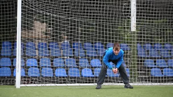 Chlapec se snaží zachytit stojící fotbalový míč na bránu