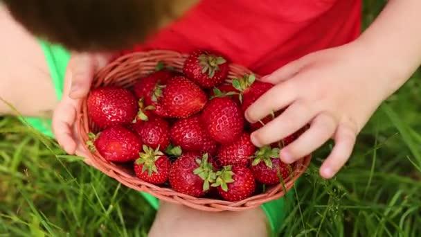 Koš s červenými jahodami a rukou malého chlapce na trávě