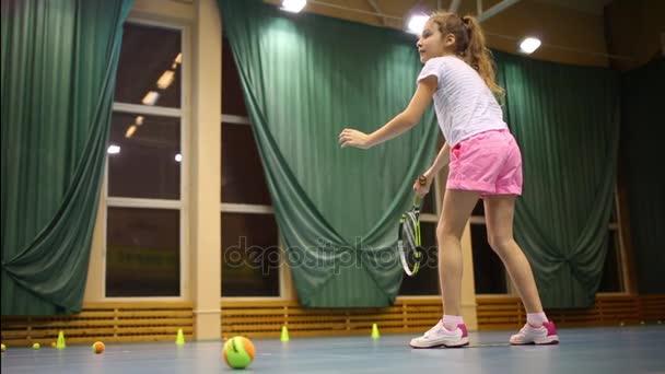 Dívka se učí onanovat koule během tenisový trénink