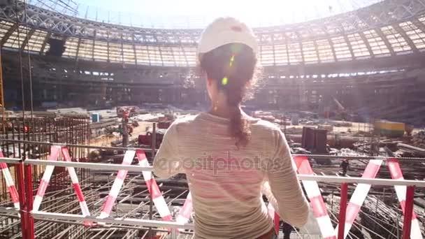 Žena v helmě pohledu na rekonstrukci stadionu
