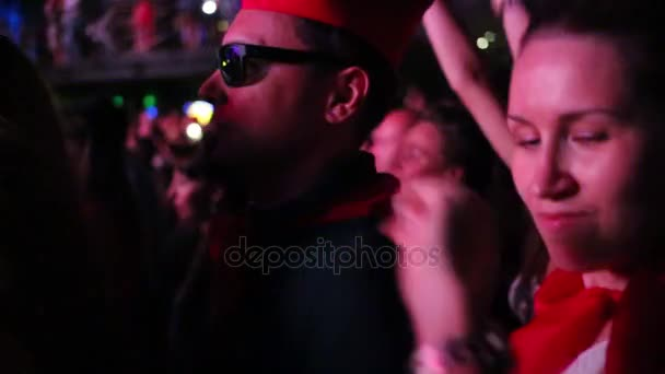 Two woman and man in sunglasses dance among other people in night club