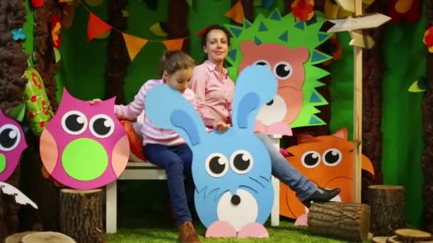 Matka a holka sedí mezi velké lepenkové zvířata a stromy