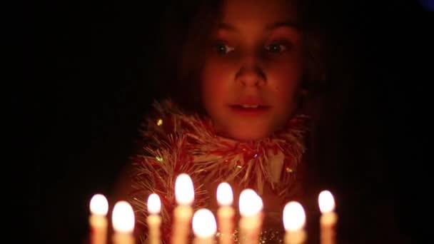 Krásná dívka sfoukne svíčky na dortu na narozeniny