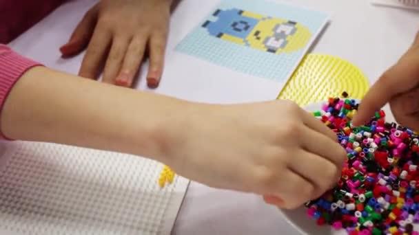 Lechischevo, Rusko - 20 Úno 2015: Děti ruce hrát mozaika a Minion schéma. Minion - je obrázek z Despicable Me 2 animovaný 3d film produkoval Illumination Entertainment pro Universal Pictures
