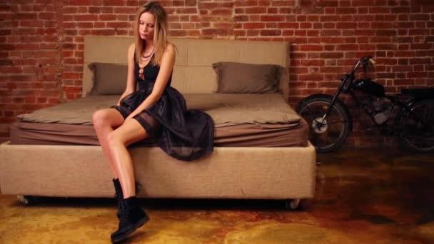 hübsche blonde Frau sitzt auf Bett und posiert im Studio