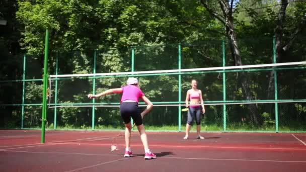 Dívka hraje badminton se svou matkou v oplocené sportovní hřiště venkovní