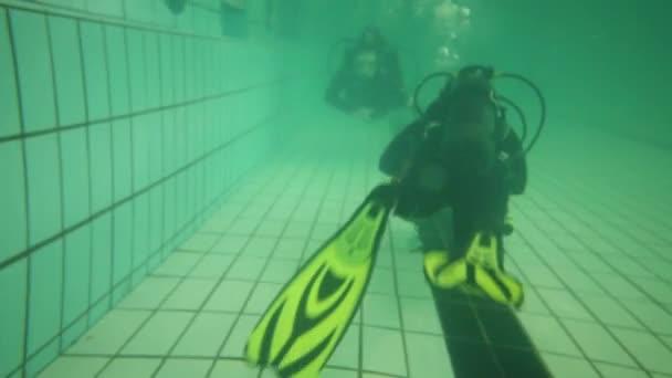 zwei Taucher in Neoprenanzügen mit Taucherbrille schwimmen auf dem Grund des Beckens