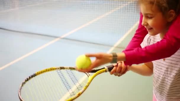 Učitelka ruce Nápověda dívku drží raketu a odrazit míč