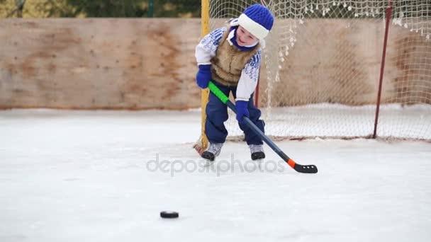 Malý roztomilý chlapec se naučí hrát hokej nedaleko brány na stadion v zimě