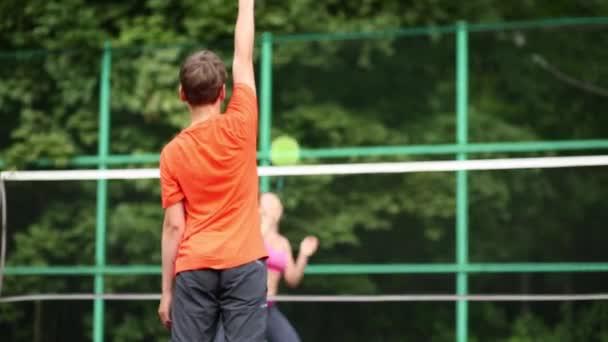Kluk hraje badminton se svou matkou na hřišti, pohled zezadu