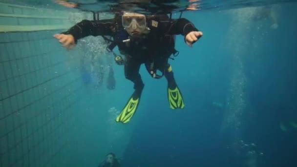 Frau taucht mit Spezialausrüstung unter Wasser in großen Pool
